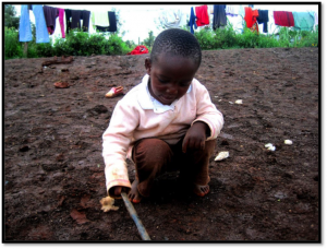 Clinton, age 3, discovering that he can still draw a picture in the dirt with a stick even though he lacks paper and felts.